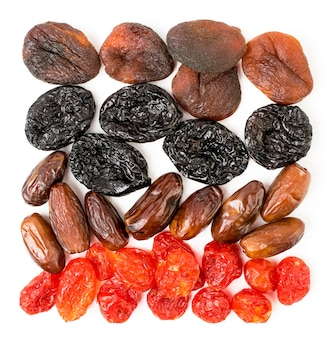 Nahaufnahme auf getrockneten aprikosen, pflaumen, hartriegel und datteln isoliert
