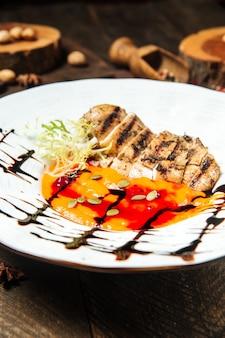 Nahaufnahme auf gourmet-hühnerbrust mit erbsenbrei-sauce und kürbiskernen