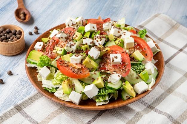 Nahaufnahme auf großem teller mit leckerem salat: tomate, feta-käse, avocado, spargel und gemüse. lebensmittel foto hintergrund.