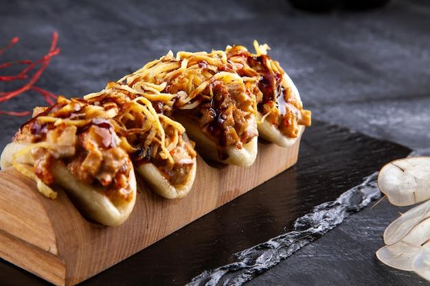 Nahaufnahme auf gua bao, gedämpfte brötchen mit fleisch. bao serviert mit leckerem topping im dunkeln. asiatische küche. asiatisches sandwich gedämpftes gua bao. fast food im japanischen stil. selektiver fokus