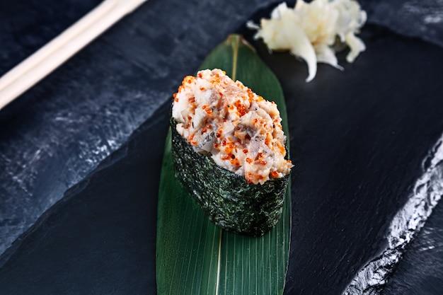 Nahaufnahme auf gunkan-sushi mit würziger sauce und aal auf dunkler steinoberfläche