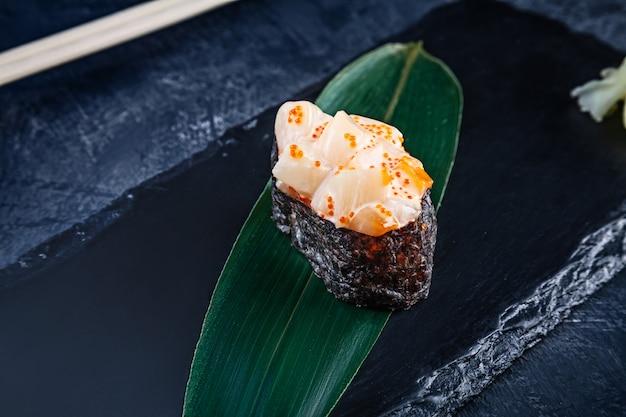 Nahaufnahme auf gunkan-sushi mit würziger sauce und jakobsmuschel auf dunkler steinoberfläche