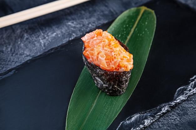 Nahaufnahme auf gunkan-sushi mit würziger sauce und lachs auf dunkler steinoberfläche