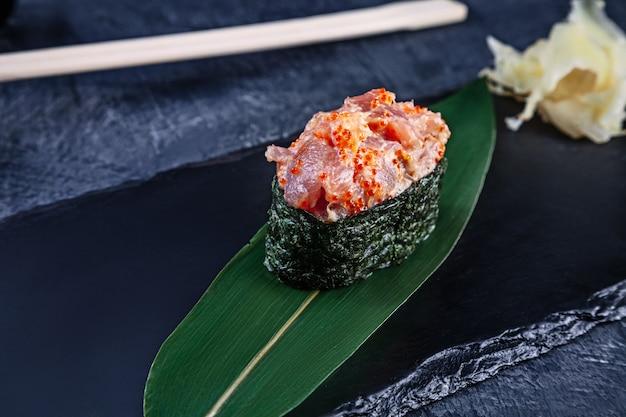 Nahaufnahme auf gunkan-sushi mit würziger sauce und thunfisch auf dunkler steinoberfläche