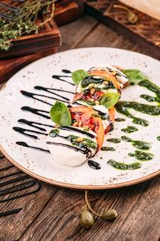 Nahaufnahme auf italienischem caprese-salat mit pesto-soße auf dem holztisch