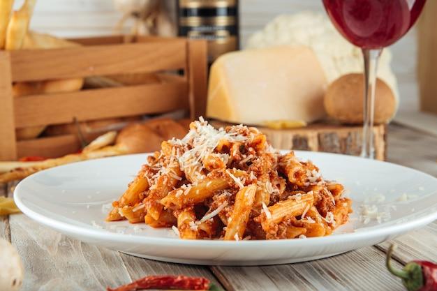 Nahaufnahme auf italienischem penne pasta bolognese rindfleisch und parmesan