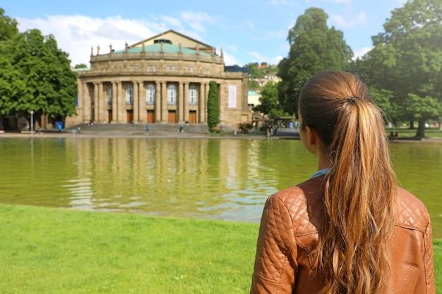 Nahaufnahme auf junge frau, die das theater von stuttgart in deutschland betrachtet