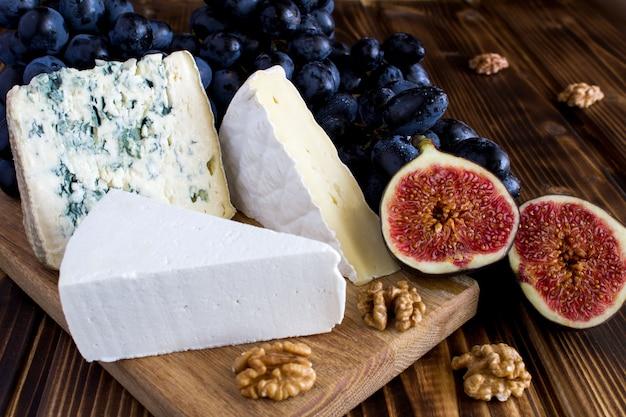 Nahaufnahme auf käse und früchten auf dem holztisch