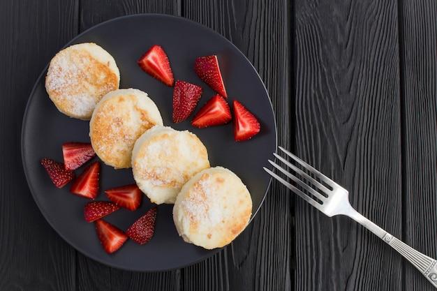 Nahaufnahme auf käsepfannkuchen und erdbeeren