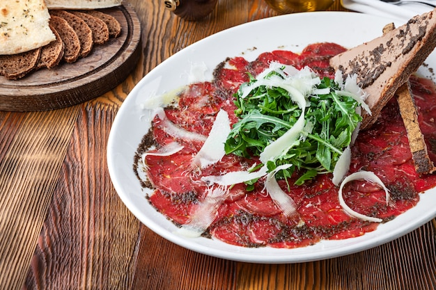 Nahaufnahme auf kalbscarpaccio mit parmesan und toast. rohes rinderfilet mit soße auf hölzernem hintergrund mit kopienraum. frischer snack der italienischen küche