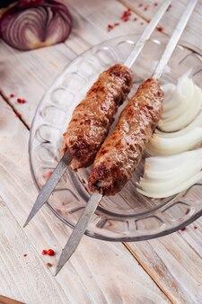 Nahaufnahme auf kaukasischen gegrillten fleischspießen lula kebab auf dem hellen holztisch