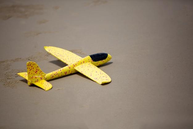 Nahaufnahme auf kinderspielzeugflugzeug, das auf dem strandsand gleitet.