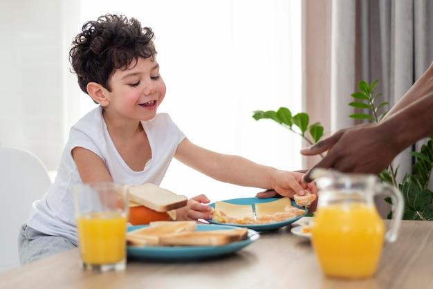 Nahaufnahme auf kleinen jungen, der tost zum frühstück isst
