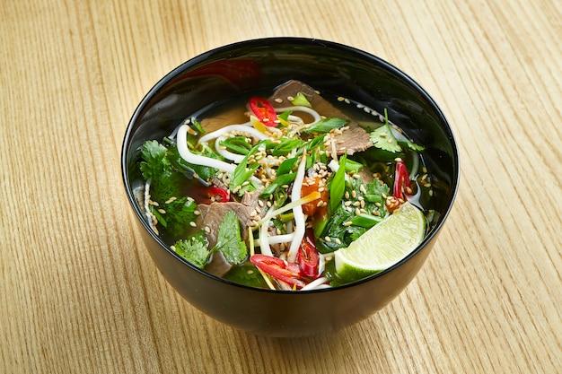 Nahaufnahme auf leckere, traditionelle pho vietnamesische suppe bestehend aus brühe, reisnudeln, kräutern und fleisch