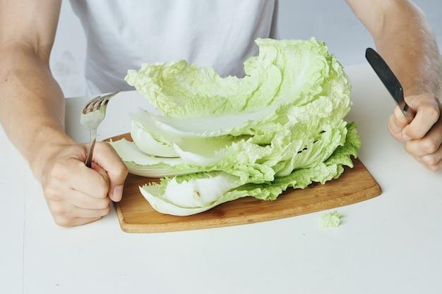 Nahaufnahme auf mann, der am tisch mit salat vor ihm sitzt