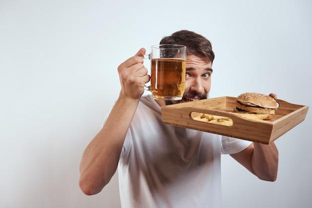 Nahaufnahme auf mann mit einem tablett mit junk food und bier