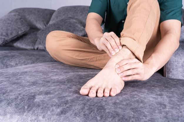 Nahaufnahme auf mannhand, die knöchelverstauchung berührt