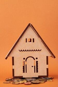 Nahaufnahme auf miniaturhausmodell und münzen
