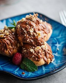 Nahaufnahme auf puddingkuchen gegossen mit geschmolzener schokolade und nüssen