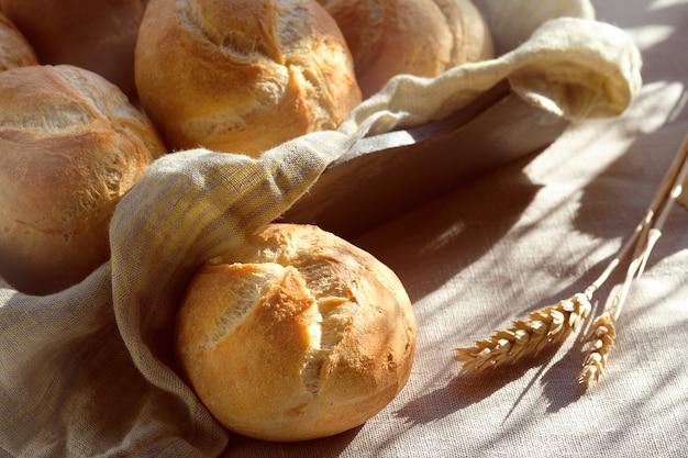 Nahaufnahme auf rostigem runden brötchen, kaiser- oder wiener rollen auf tisch mit leinentischdecke bedeckt