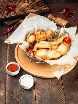 Nahaufnahme auf russischen snacks mini gebratenen kuchen chebureki mit sauce auf dem holztisch