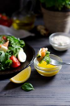 Nahaufnahme auf salat auf gabel in sauce getaucht
