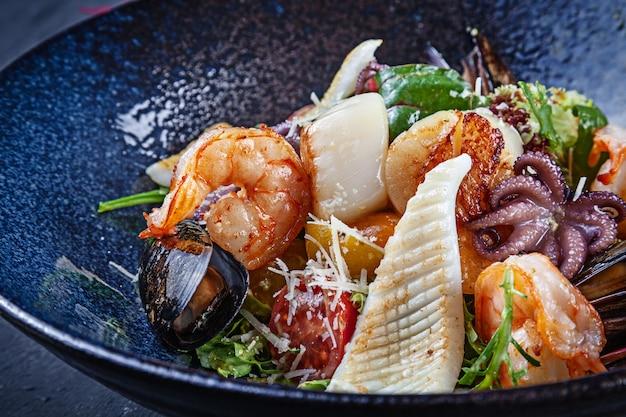Nahaufnahme auf salat mit meeresfrüchten in dunkler schüssel serviert. lebensmittelfotografie für anzeigen oder rezept. speicherplatz kopieren. warmer salat mit garnelen, tintenfisch, jakobsmuschel, tintenfisch in der schüssel. mittagssnack.