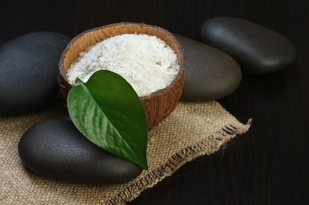 Nahaufnahme auf salz in kokosnussschale und spa-steinen