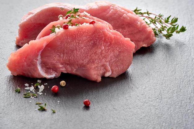 Nahaufnahme auf scheiben des rohen rindfleischs. lendenstück mit kräutern und gewürzen auf steinbrett, kopieraum.
