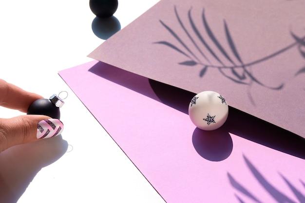 Nahaufnahme auf schwarzen und weißen weihnachtskugeln auf lila und grauem schichtpapier