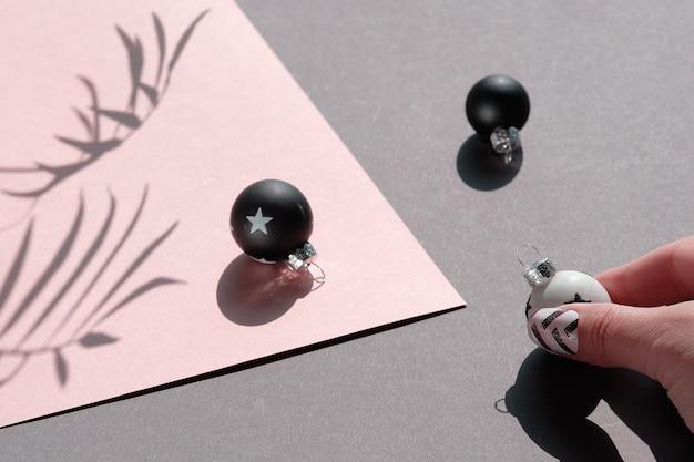 Nahaufnahme auf schwarzen und weißen weihnachtskugeln auf rosa und grauem schichtpapier.