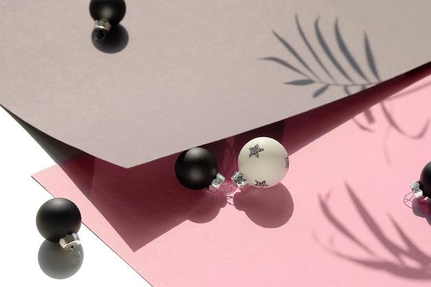 Nahaufnahme auf schwarzen und weißen weihnachtsspielzeugen auf rosa und grauem schichtpapier