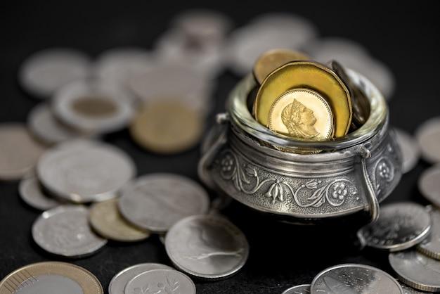 Nahaufnahme auf silbernen topf voller goldener münzen