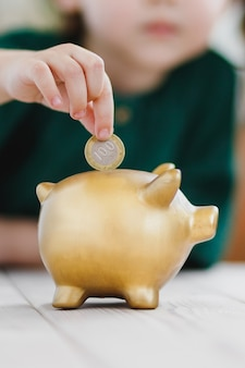 Nahaufnahme auf sparschwein und kinderhand, die eine münze in das konzept der einzahlung und des geldsparens einlegen
