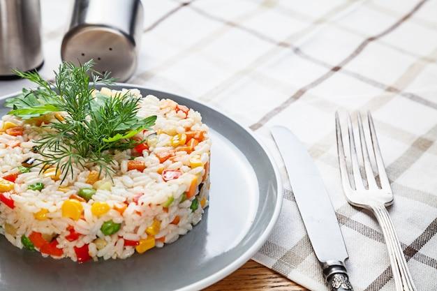 Nahaufnahme auf teller reis mit gemüse. gebratener reis des chinesischen gemüses. hausgemachtes veganes oder vegetarisches essen zum mittagessen. gesundes essen mit platz zum kopieren