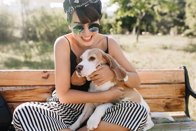Nahaufnahme-außenporträt des faszinierenden lachenden mädchens, das beagle-welpen hält, während auf bank sitzt. erfreute junge frau in der sonnenbrille, die mit hund im park spielt