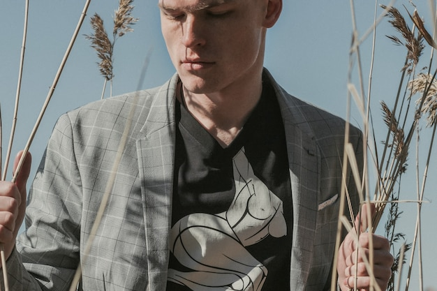 Nahaufnahme-außenporträt eines schönen jungen stilvollen mannes, der trockenes gras am seeufer hält.