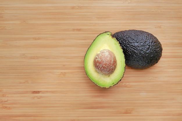 Nahaufnahme-avocado beinahe eingeschnitten auf hintergrund des hölzernen brettes.