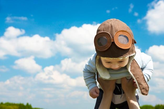Nahaufnahme, babypilot, in einem pilotenhut, helm, an den händen einer jungen frau. platz kopieren.