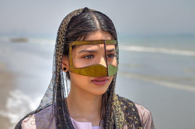 Nahaufnahme batoola, goldener schal, der gesicht bedeckt, das teil des traditionellen bandari-kostüms südiran ist.