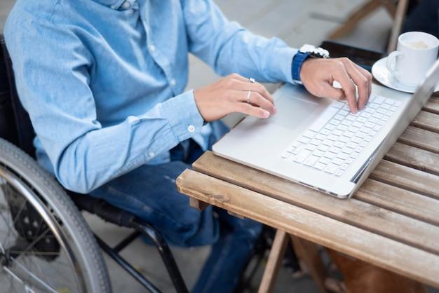 Nahaufnahme behinderter mann, der auf laptop schreibt