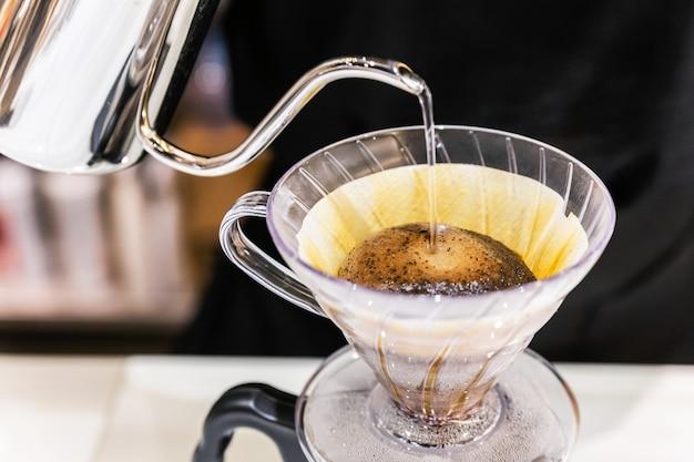 Nahaufnahme beim übergießen von kaffee mit einer alternativen methode namens tropfen. kaffeemühle, kaffeeständer und übergießen auf marmorplatte.