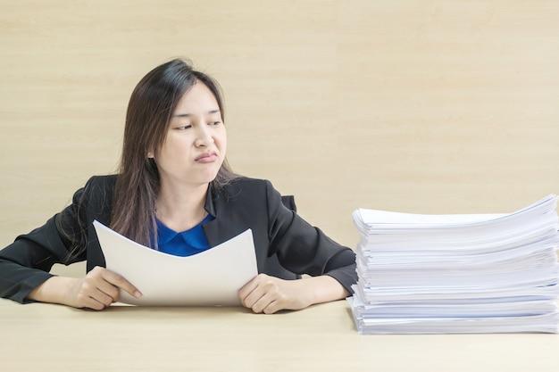 Nahaufnahme berufstätige frau gelangweilt vom stapel der arbeit