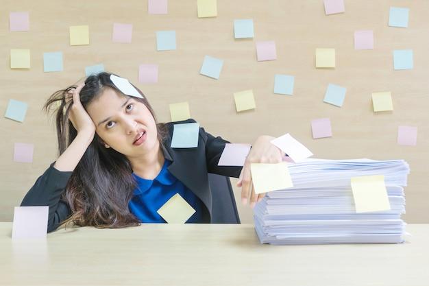 Nahaufnahme berufstätige frau gelangweilt vom stapel der harten arbeit