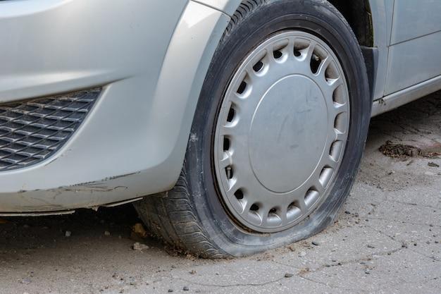Nahaufnahme beschädigter reifen. das rad des autoreifens undicht. reifenpanne wartet auf reparatur. verlassenes auto auf dem parkplatz.