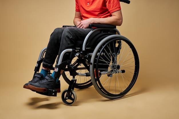 Nahaufnahme beschnittener behinderter mann auf rollstuhl, freizeitkleidung tragend, allein. behinderte männliche copes ohne die unterstützung von irgendjemandem