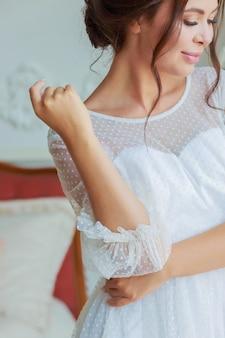 Nahaufnahme beschnittenes porträt der braut im weißen hochzeitskleid mit nachdenklichem blick nach unten