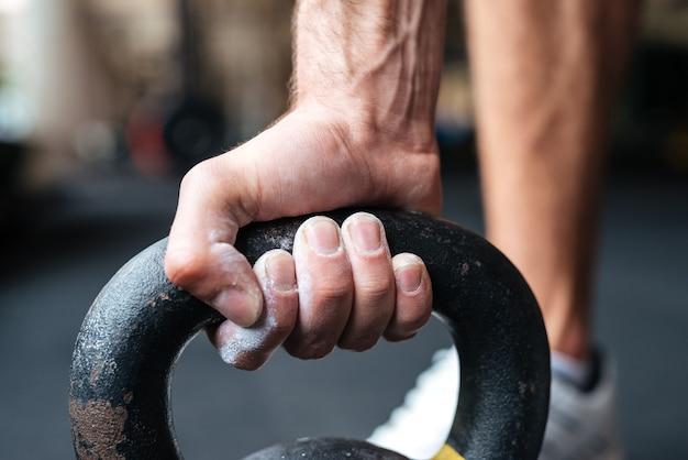 Nahaufnahme bild fitness hand und kettlebell. vorbereitung auf die erhöhung