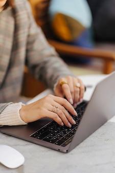 Nahaufnahme bild von frauenhänden tippen und schreiben auf laptop, arbeiten am café.