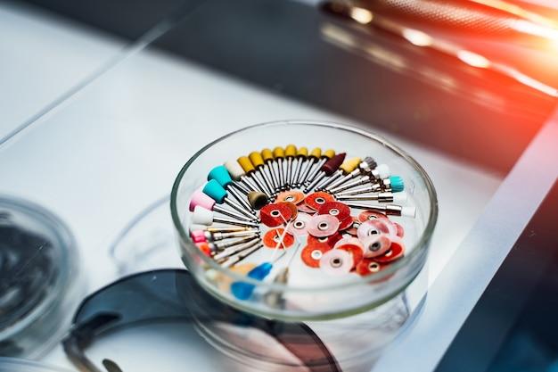 Nahaufnahme bild von zahnärztlichen instrumenten. bohrer und nadeln zur wurzelkanalbehandlung auf glasplatte